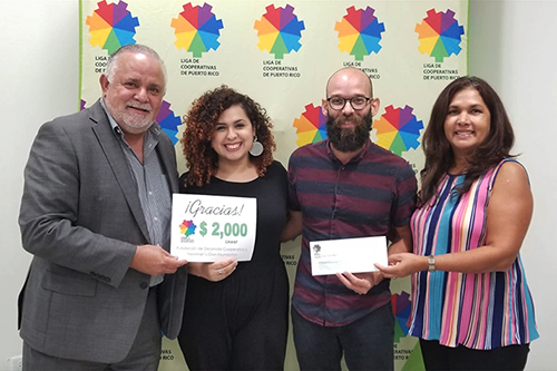 Recipients of La Liga de Cooperativas in Puerto Rico accept a donation from money raised by food co-ops and their partners in the natural and organic products industry. [photo: NCG]