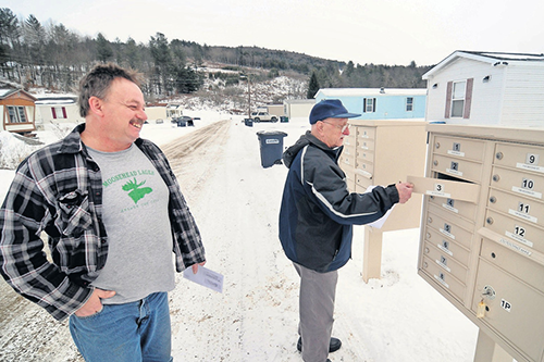 Neighbors Ronald Dickson, left, and Alston Douglass check the mail at the manufactured home park they now own with fellow residents. [photo: Stefan Hard]