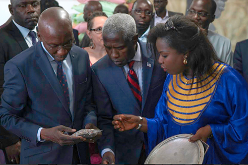 Ambassador Mushingi inspects seeds during the launch of the Feed the Future Kawolor project.
