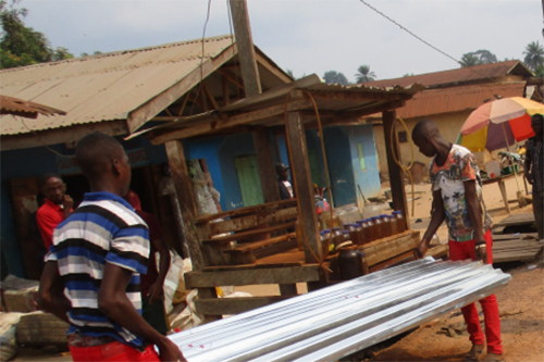 Members of Sebhill Cooperative load roofing material for a customer. [photo: Marketlinks]