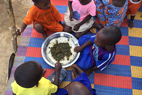 Children in Senegal enjoy community meal put on by a Mother's Group to showcase nutritious recipes as part of NCBA CLUSA's Feed the Future Project.