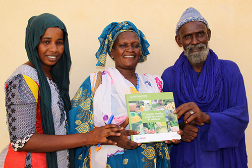 Aissata, left, a nutrition volunteer and CBSP, poses with the new cookbook alongside members of her community, including the Citizen Working Group coordinator Mamdou Bocar Dia, right. [photo: Feed the Future]
