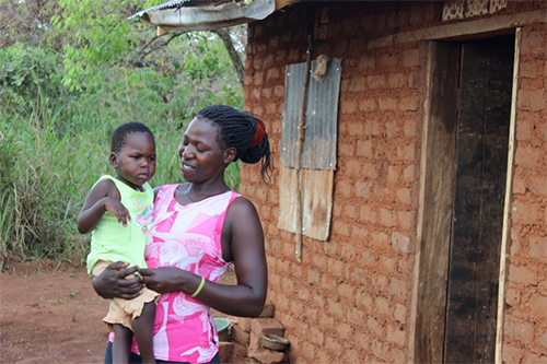 Juliet Abitegeka and her child now have a roof over their heads, thanks to the training she received in agriculture, business and financial management through NCBA CLUSA's YETA project.